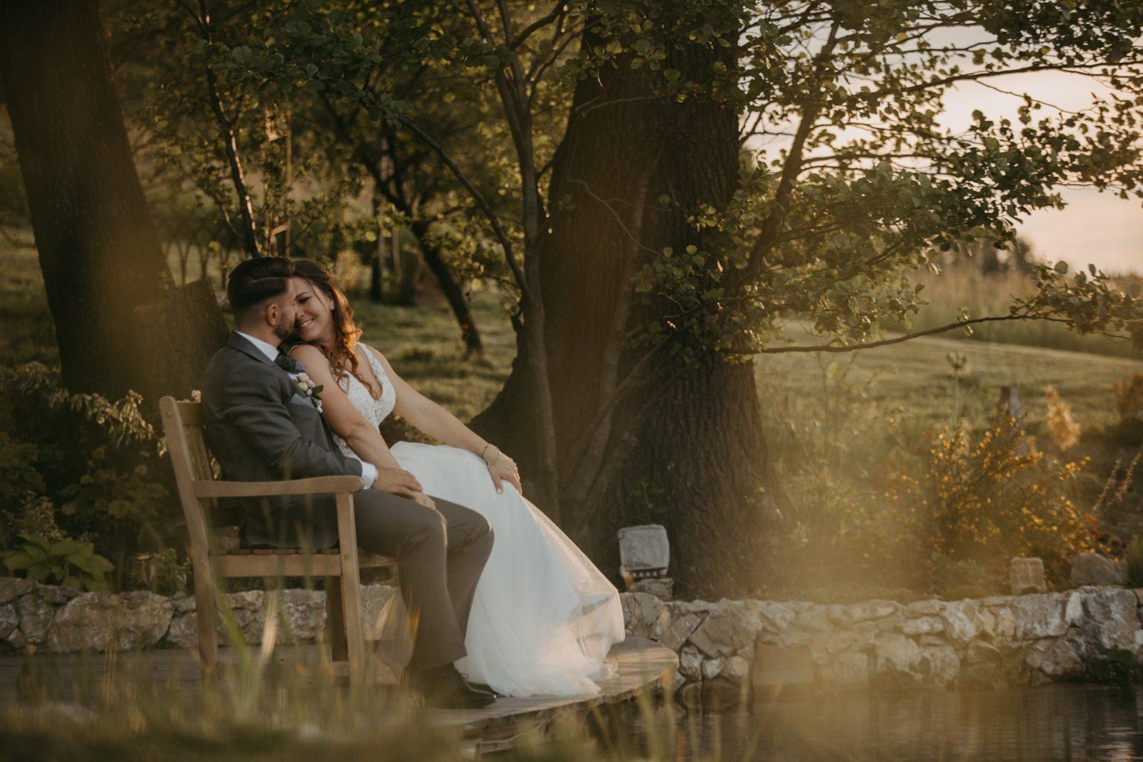 Brautpaar sitzt auf einer Bank bei einem Teich